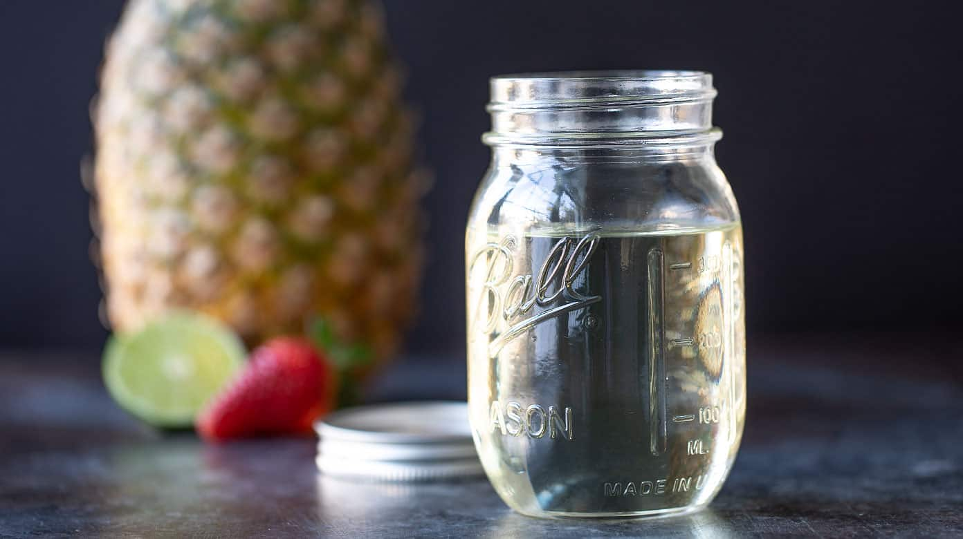 A jar filled with simple syrup.  A pineapple, lime and strawberry are in the background.