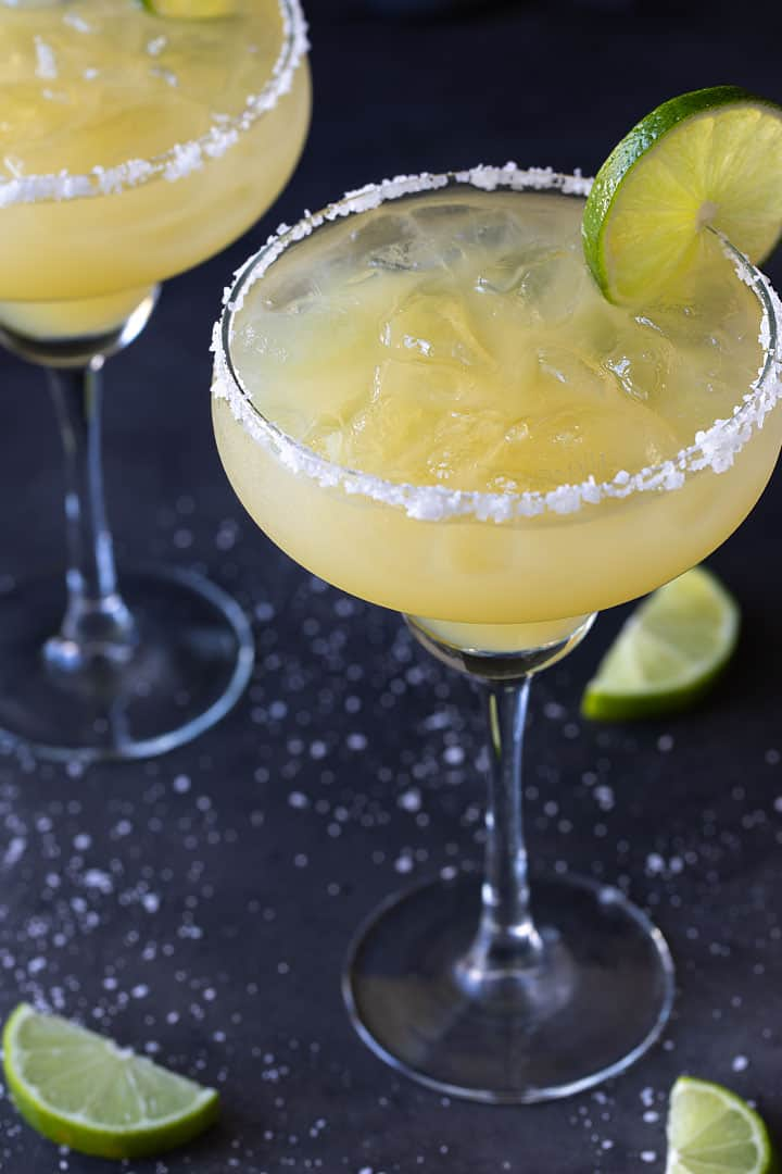 Two non-alcoholic margaritas in glasses rimmed with salt and garnished with lime wheels on a black background.