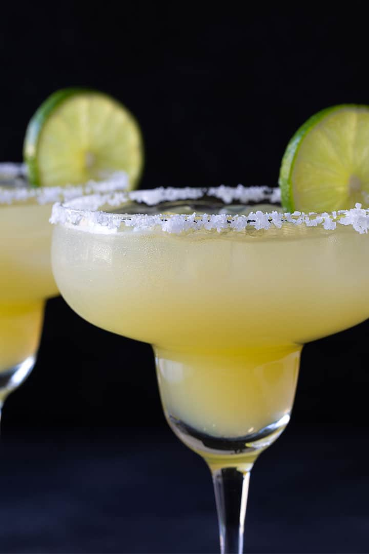 A closeup view of a margarita mocktail in a glass rimmed with salt and garnished with a lime wheel.