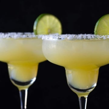 Two virgin margarita mocktails in glasses rimmed with salt on a black background.
