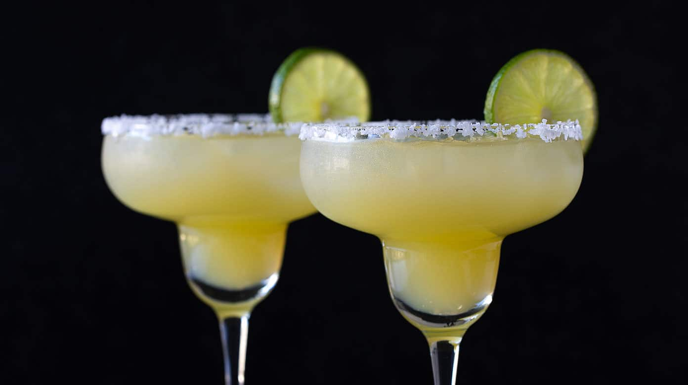 Two virgin margarita mocktails in glasses rimmed with salt and garnished with lime wheels on a black background