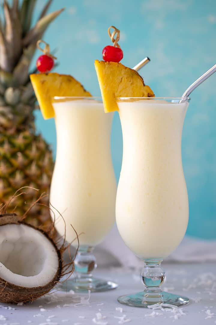 Two pina coladas in hurricane glasses beside a coconut and fresh pineapple.