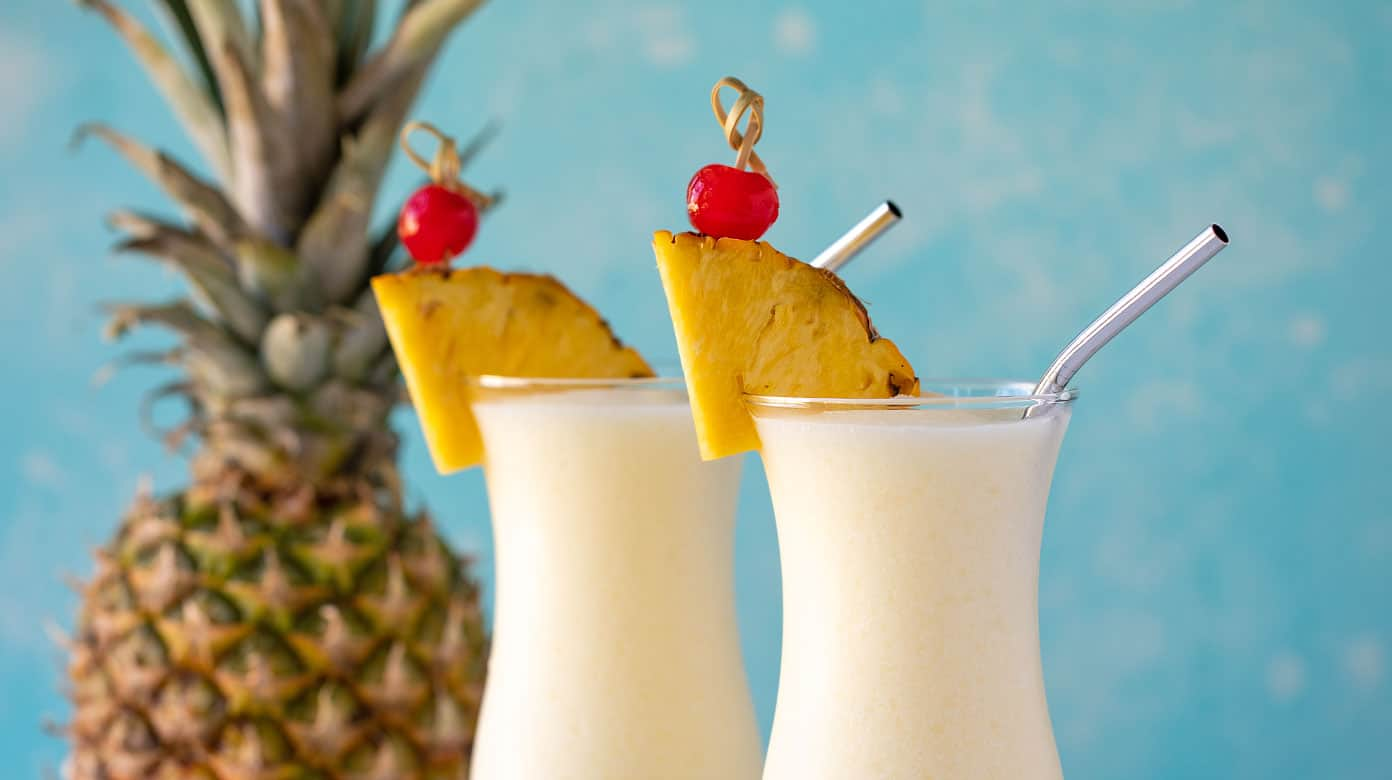 Two pina coladas in glasses with stainless steel straws.  A fresh pineapple is in the background.