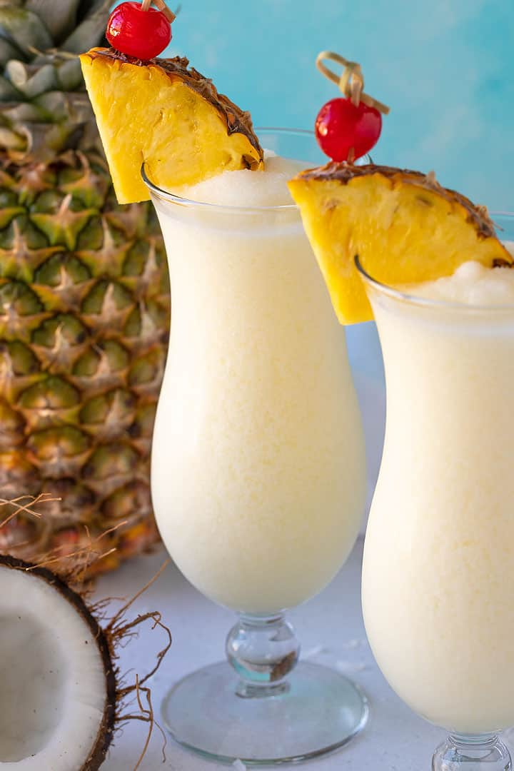 Two pina coladas garnished with fresh pineapple and maraschino cherries beside a coconut and pineapple.