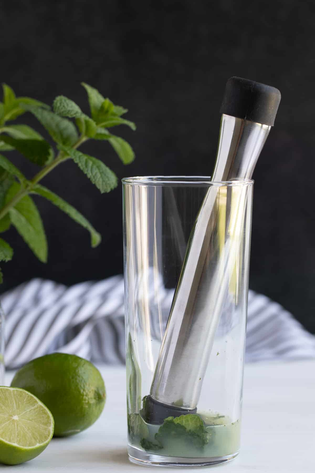 Front view of a stainless muddler in a glass with fresh mint and lime juice.
