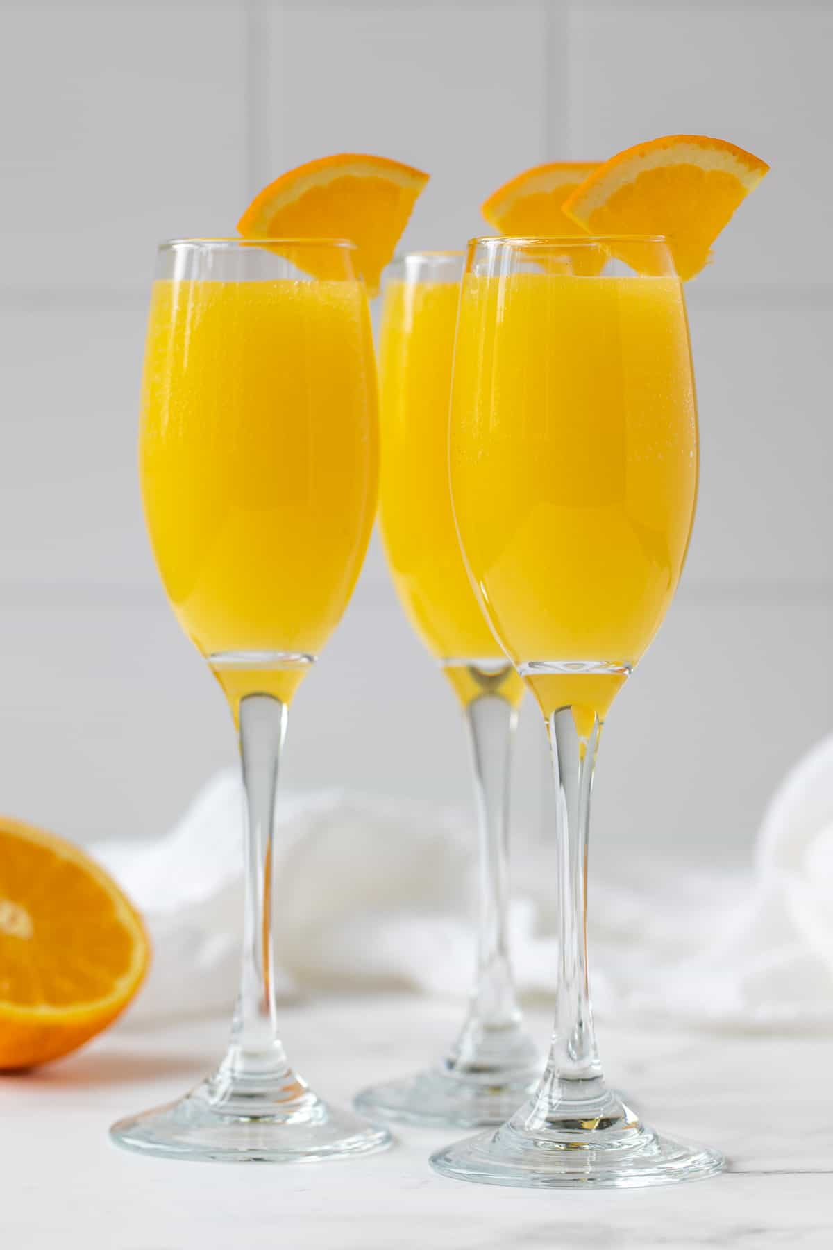 Front view of three mimosas in champagne flutes.