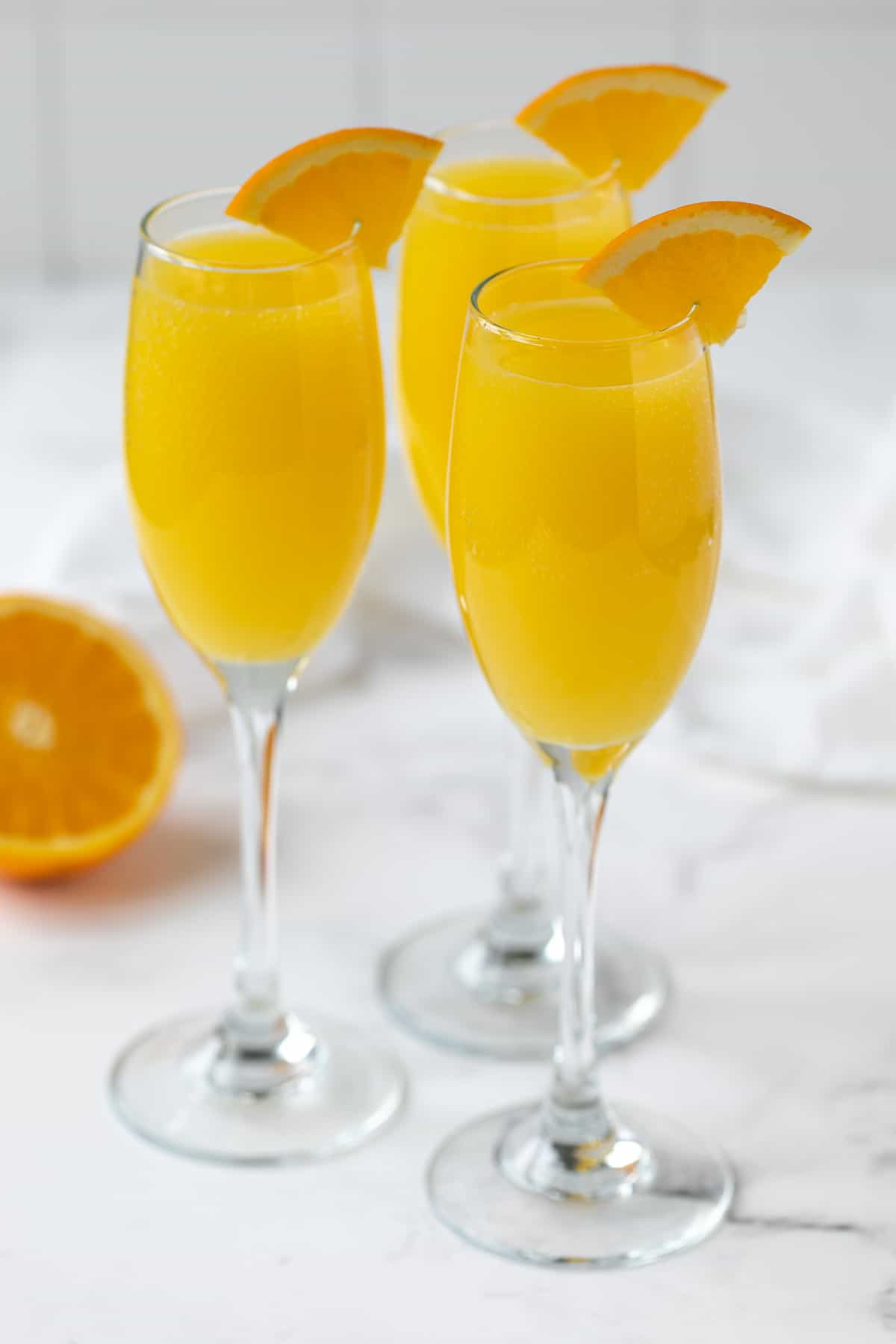 Three mimosas garnished with an orange slice on a white marble surface.