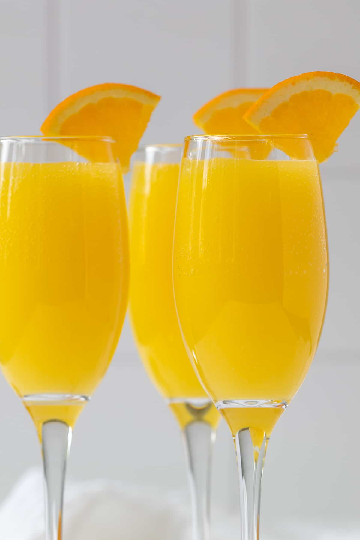 Front closeup view of three garnished mimosas in champagne flutes.