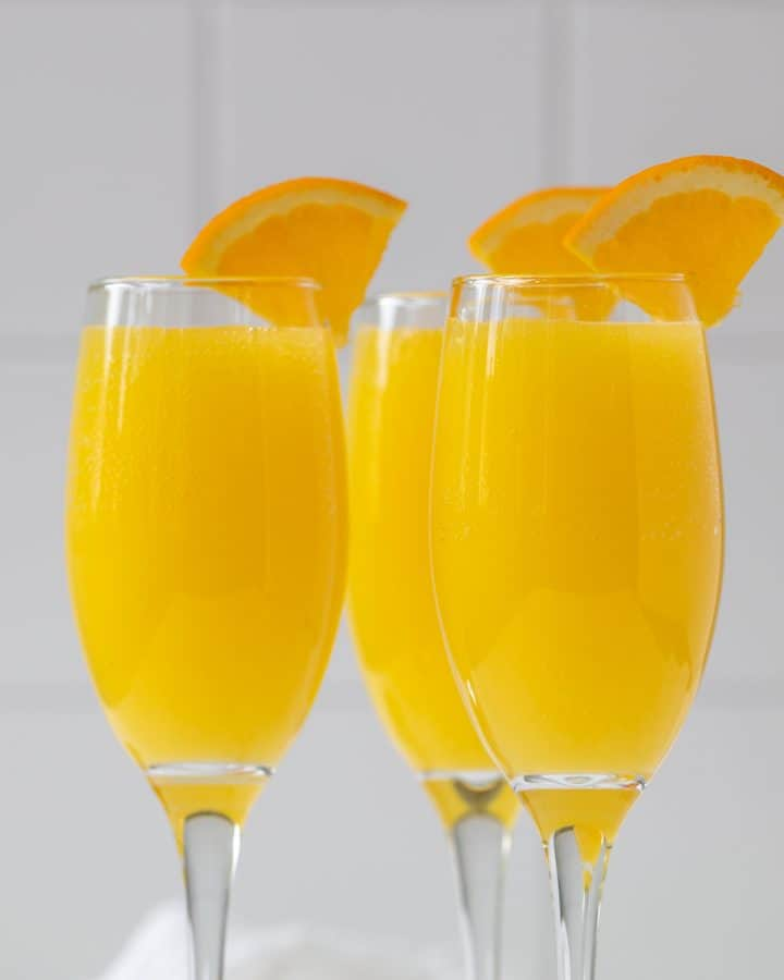 Closeup view of three mimosas garnished with orange slices.
