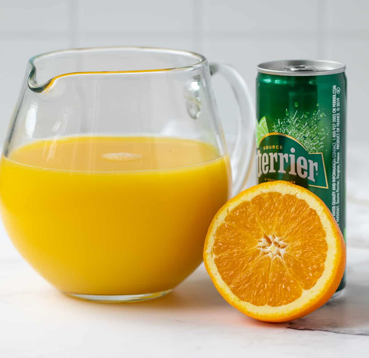 A glass pitcher of orange juice, a sliced orange and a can of sparkling water.